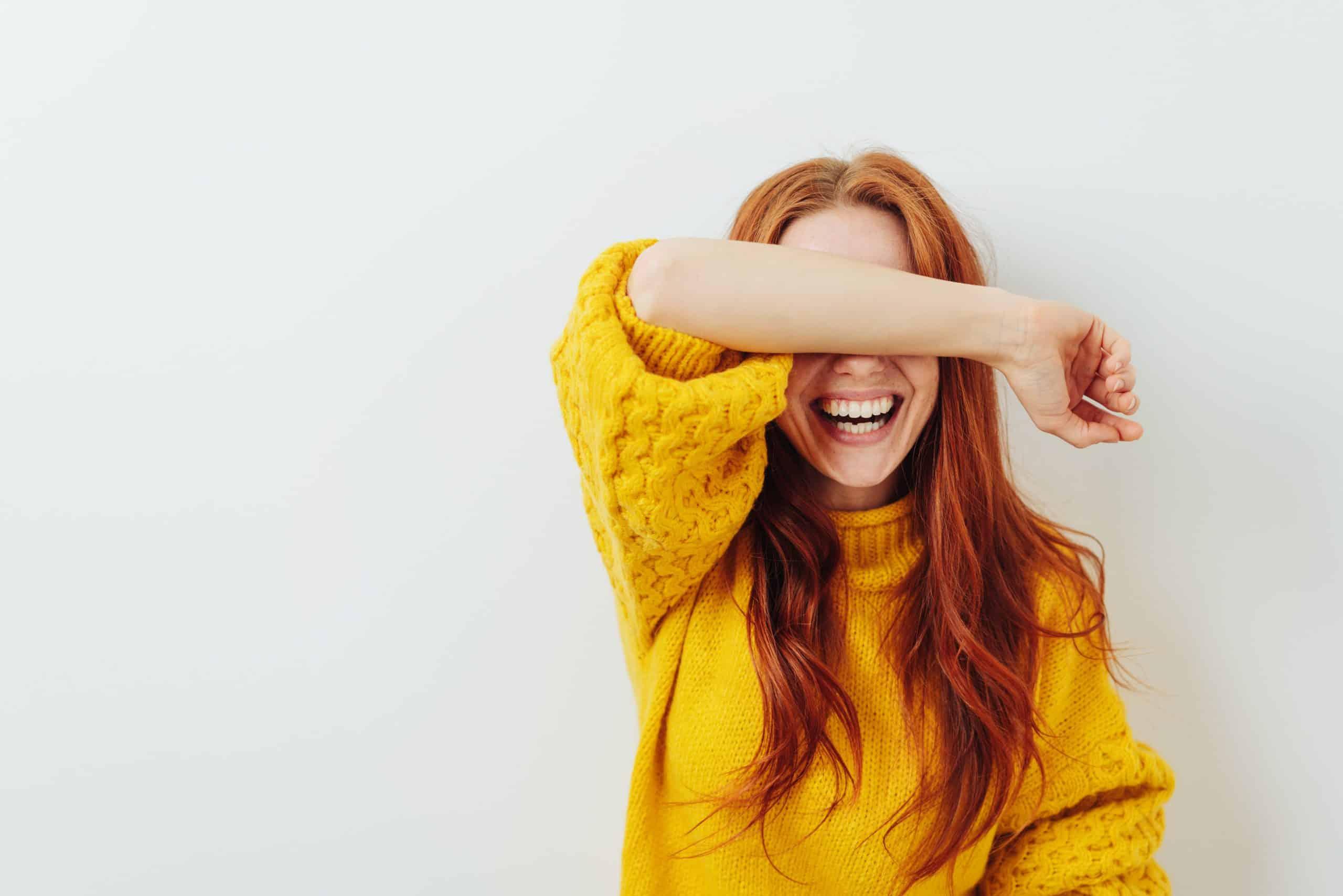 femme timide en haut jaune couvrant ses yeux avec son bras