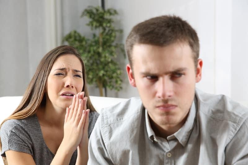 Femme demandant pardon à un homme après un conflit assis sur un canapé dans le salon d'une maison