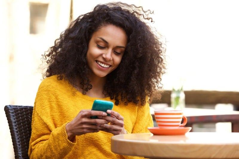 Portrait de la belle jeune femme afro-américaine écrit un message texte sur téléphone mobile au café