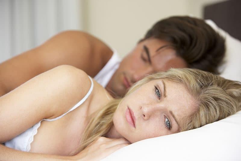 femme inquiète couchée dans son lit pendant que l'homme dort