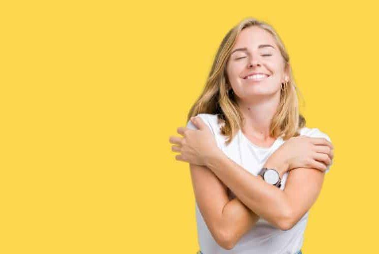 Belle jeune femme portant un t-shirt blanc décontracté se serrant sur fond isolé
