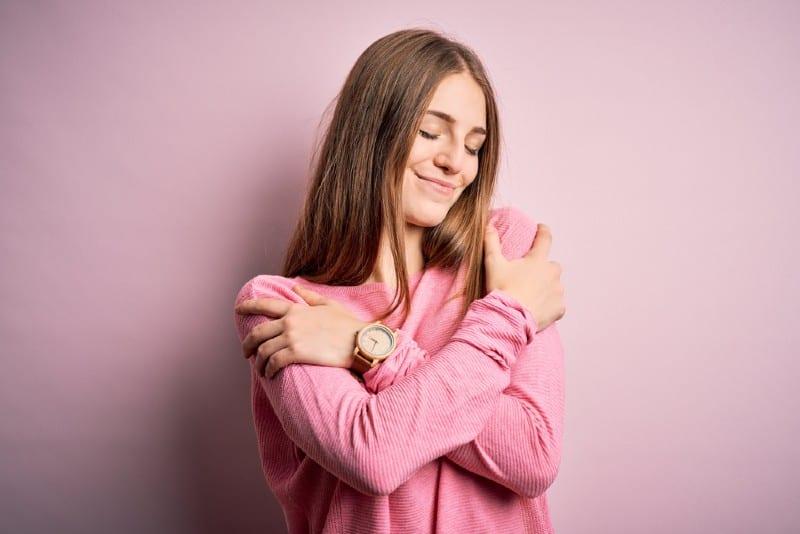 Belle jeune femme rousse portant un pull décontracté se serrant sur fond rose isolé