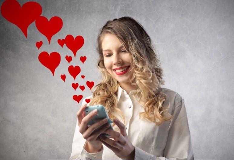 Femme souriante envoie des sms d'amour avec un téléphone mobile