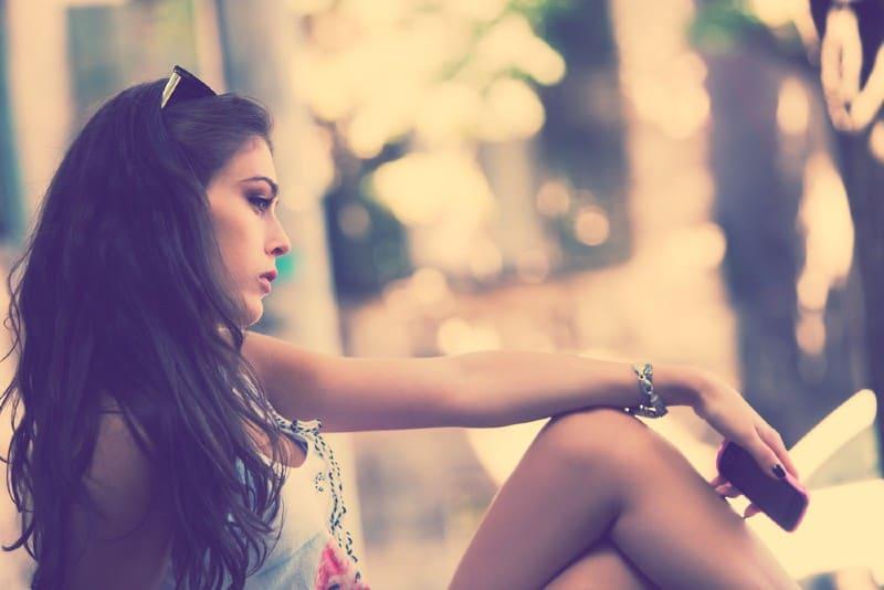 femme triste assise à l'extérieur