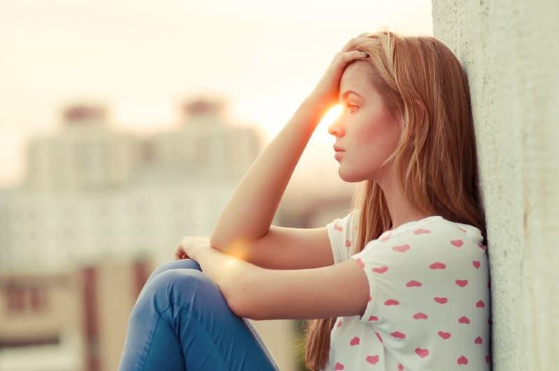 une jeune femme triste assise près de la fenêtre