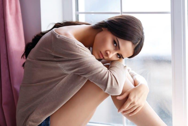 Jolie jeune fille de mauvaise humeur assise sur le rebord de la fenêtre et s'appuyant sur ses jambes tout en réfléchissant