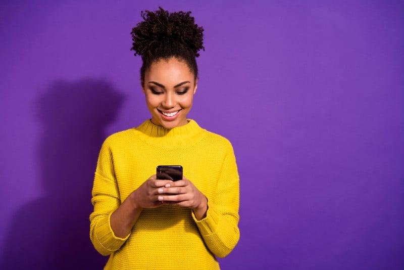 fille tenant le téléphone dans les mains et envoyer des SMS