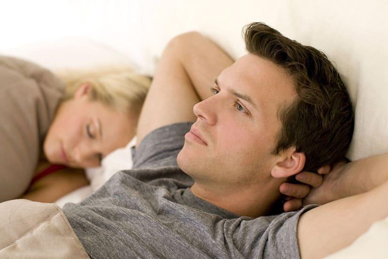 homme inquiet pensant pendant que la femme dort
