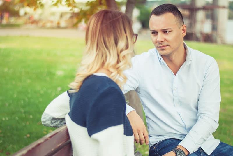 homme sérieux parlant à une femme dans le parc