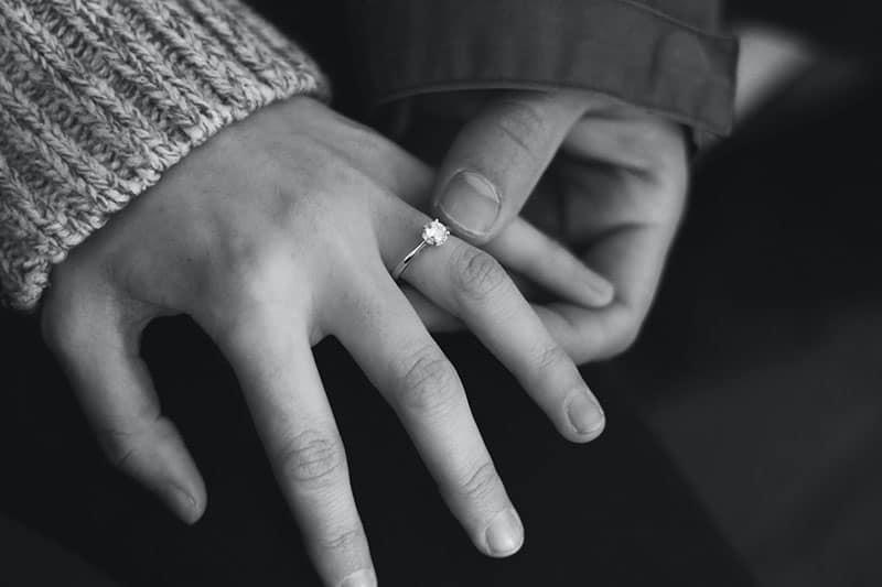 homme tenant la main de la femme avec bague de fiançailles dessus