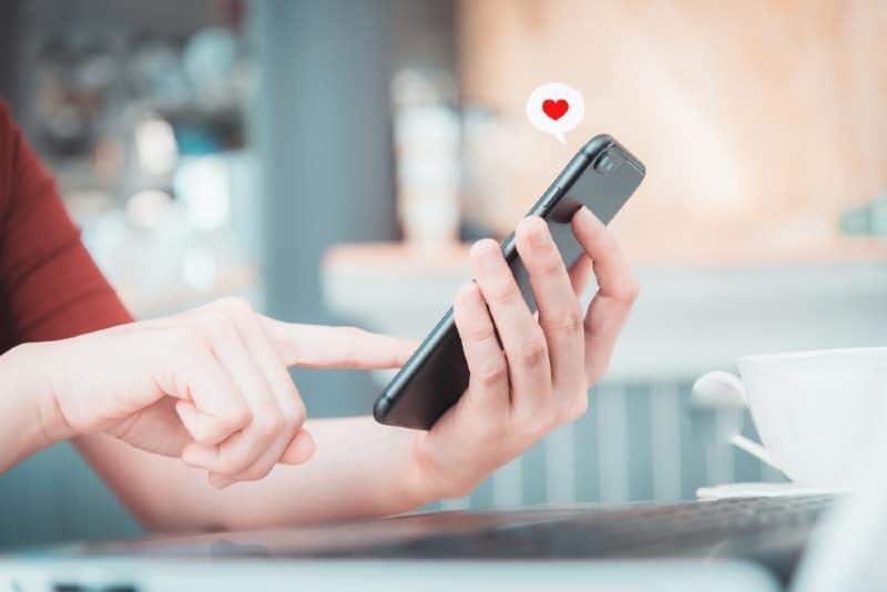 Gros plan d'une main de femme textos message d'amour sur smartphone