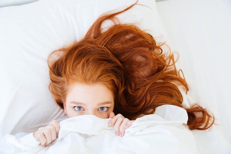 rousse jeune femme couchée dans son lit et se cachant sous le drap