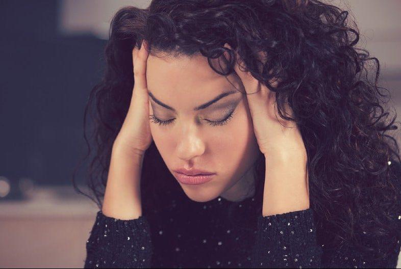 Portrait de jeune femme triste a souligné en gardant sa tête dans ses mains