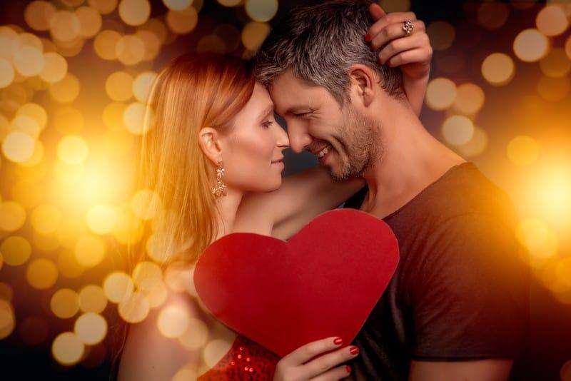 couple étreindre et tenant coeur rouge