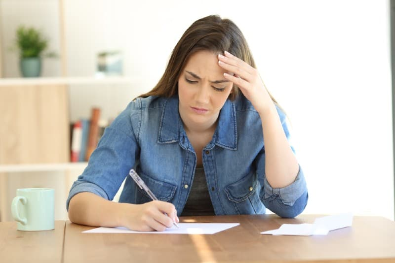 Une femme triste écrivant une lettre sur une table à la maison