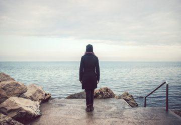 femme solitaire debout au bord de la mer