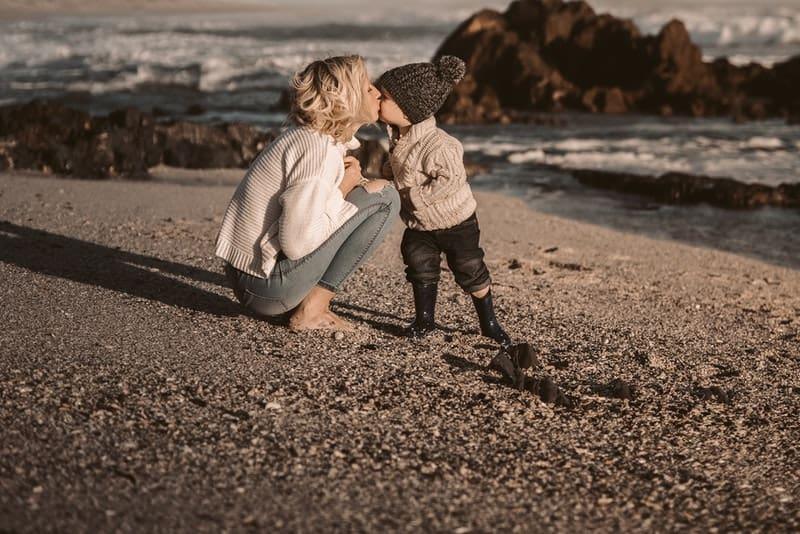 une maman blonde embrasse son bébé sur la plage