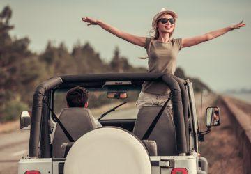 Une fille avec des lunettes de soleil se tient avec les bras tendus dans une jeep sans toit pendant la conduite