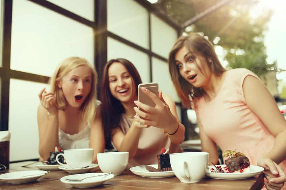 Des amis sont assis en train de boire du café en train de manger un gâteau et de se demander quelque chose au téléphone