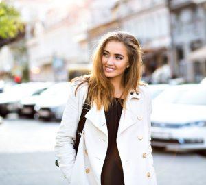une femme aux cheveux bruns dans un manteau marche dans la rue