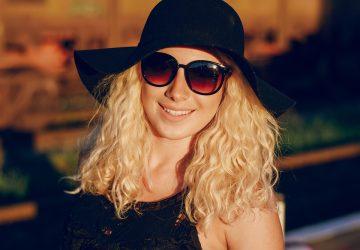 une femme blonde avec un chapeau noir