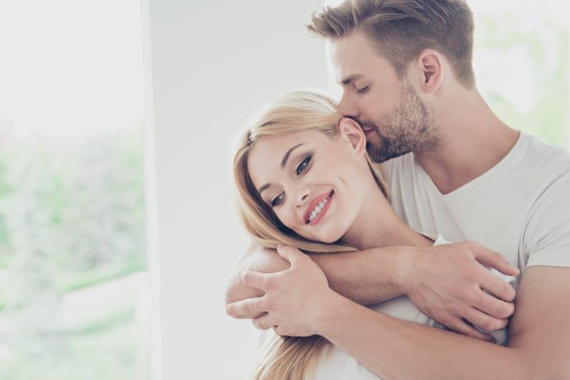 un homme qui embrasse une fille derrière son dos et l'embrasse sur la tête
