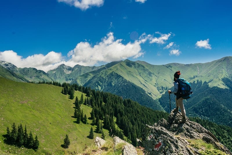 l'alpiniste se tient sur un rocher et regarde la montagne devant lui