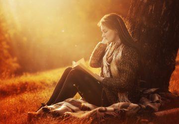 la fille est assise sous un arbre et lit un livre