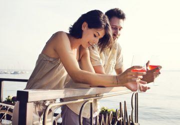 un homme et une femme se tiennent sur la clôture et parlent