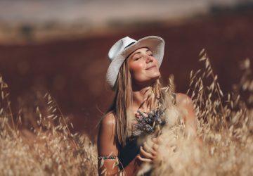 une femme avec un chapeau est assis dans un champ de blé