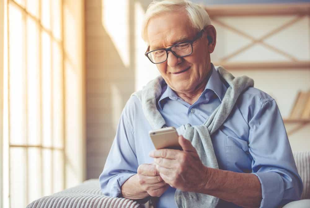 Un homme plus âgé souriant lit un message sur son téléphone portable