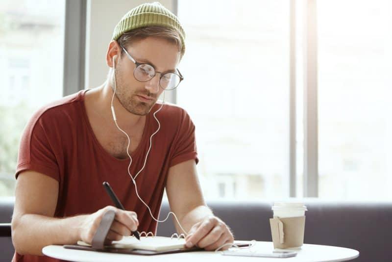 un homme avec des écouteurs dans les oreilles s'assied et écrit
