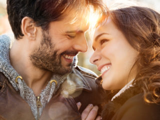 un couple souriant embrassant regarde et rit