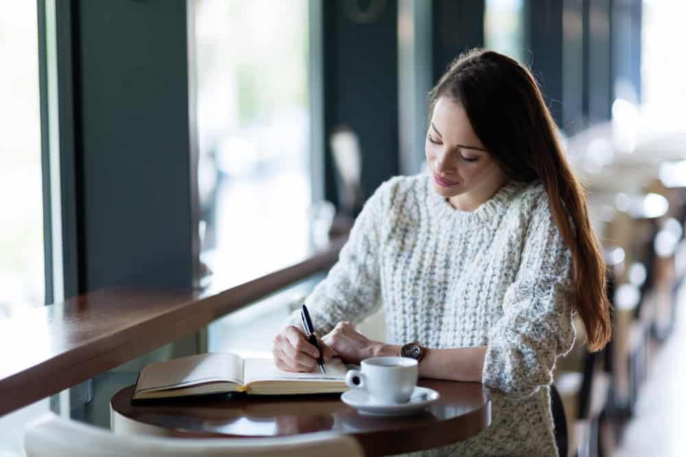 Une femme assise à une table de boire du café et d'écrire un journal