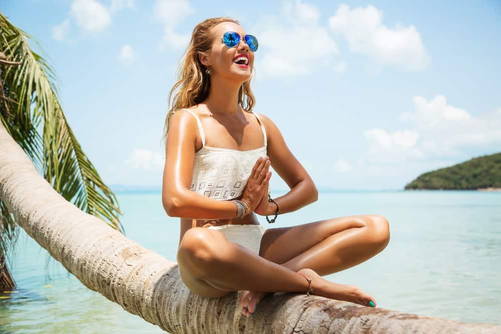 Une femme aux cheveux blonds assis sur un palmier en bikini
