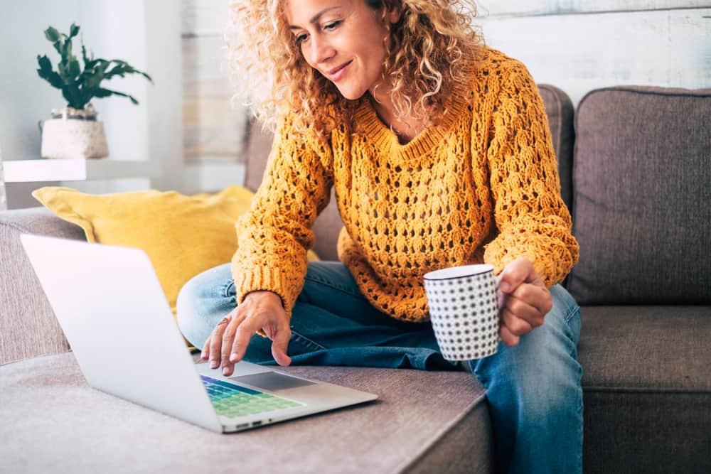 Une femme dans un camion benne jaune de boire du café et assis à un ordinateur portable
