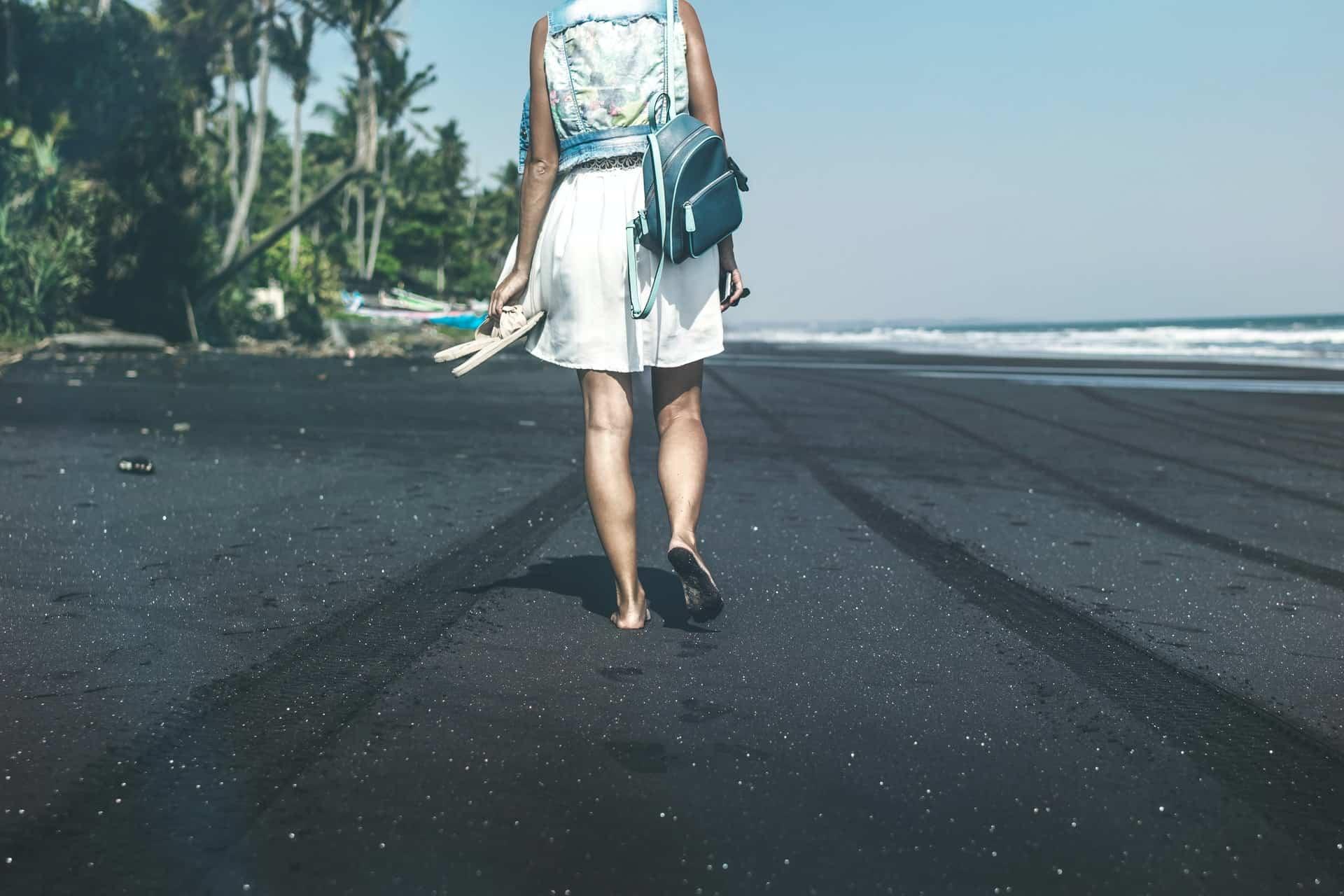Une femme marche pieds nus sur la plage avec des pantoufles à la main