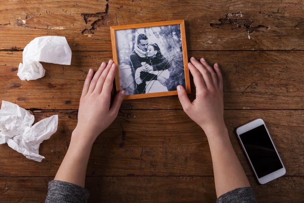 Une femme tenant une photo cassée dans ses mains sur une table à côté d'un téléphone portable et deux mouchoirs