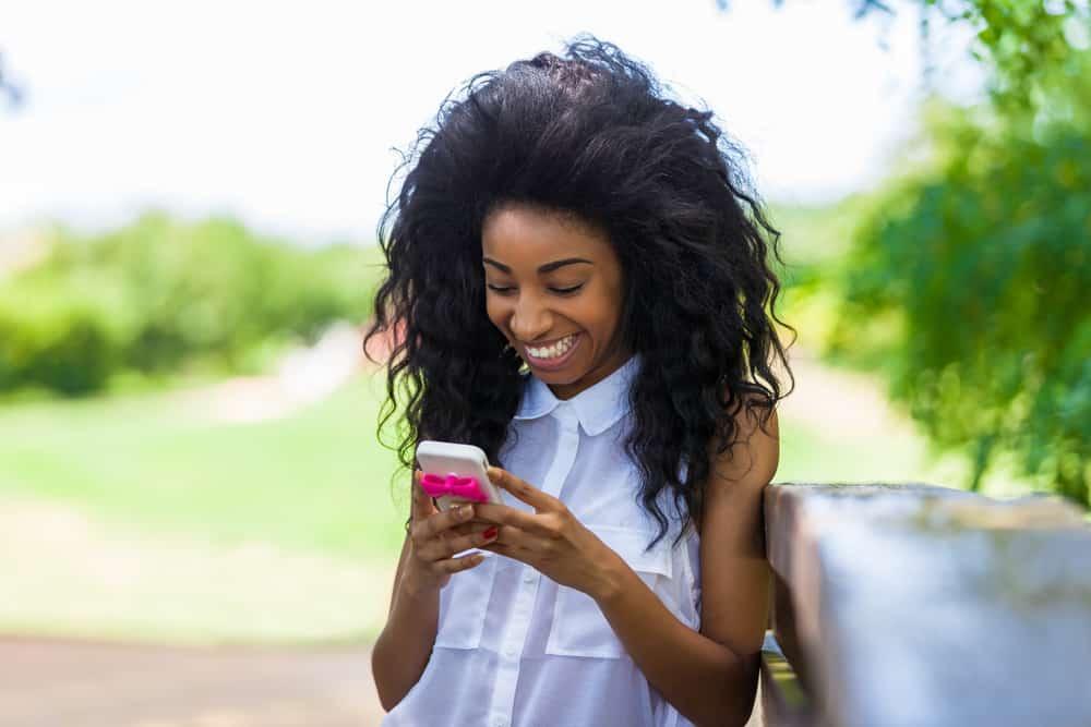 belle femme noire souriante aux cheveux luxuriants écrit des sms