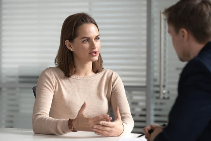 belle jeune femme parlant à l'homme au bureau