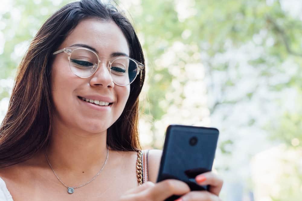 brune souriante écrit des sms