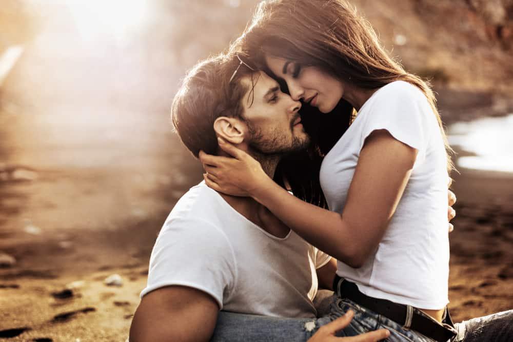 couple amoureux assis sur la plage et s'embrasser