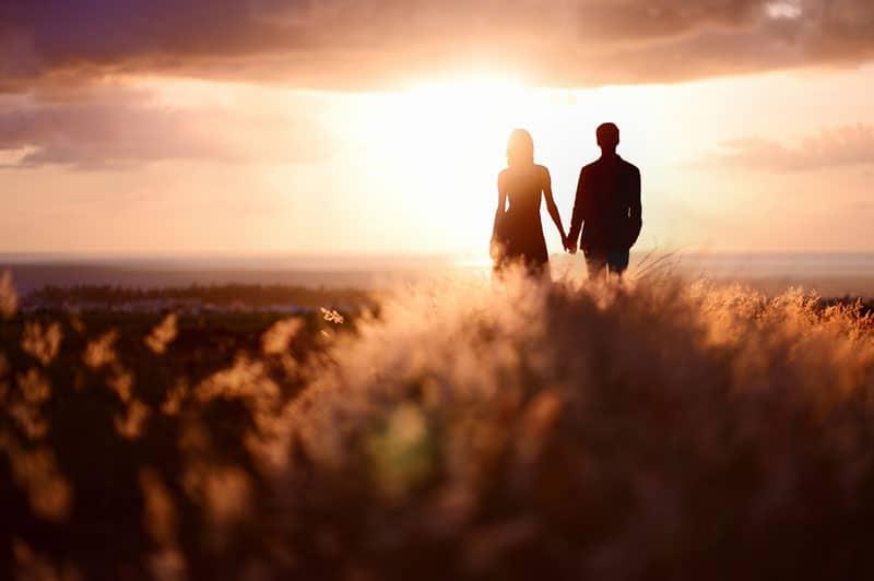 couple appréciant le coucher du soleil dans le pré