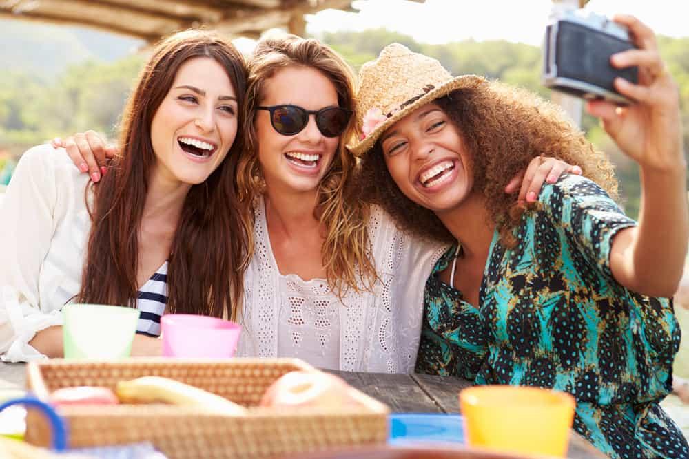 des amis s'assoient pour prendre un café et rient en prenant des photos