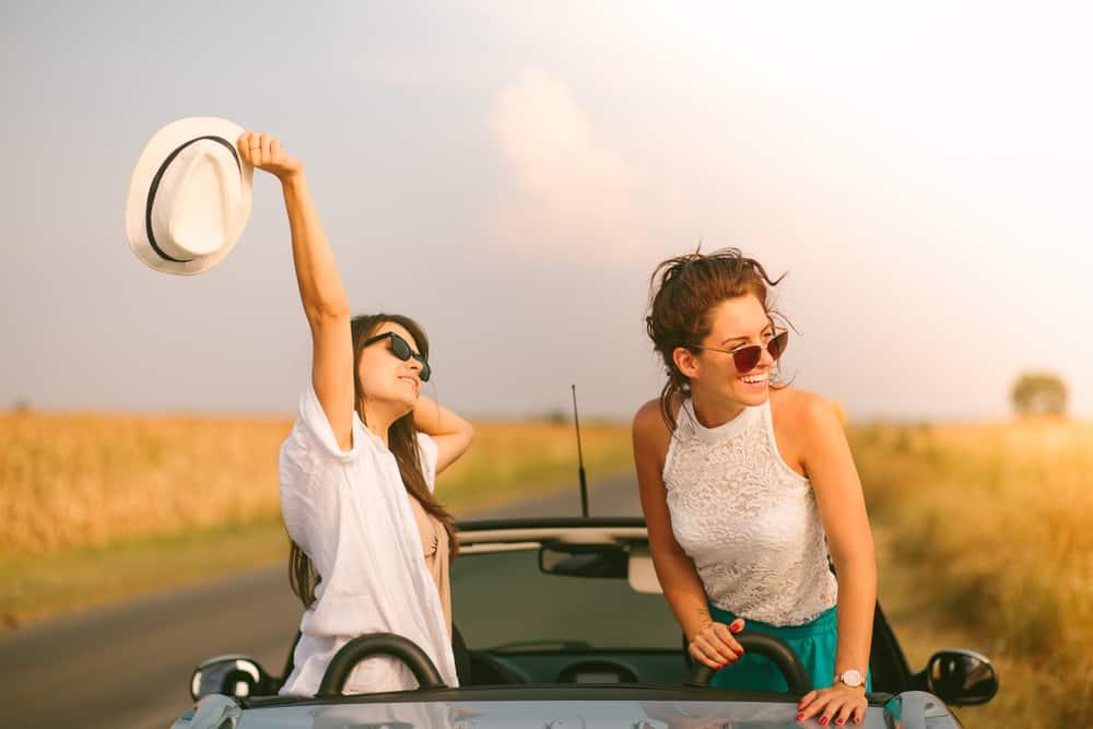 deux femmes conduisent une voiture et rient
