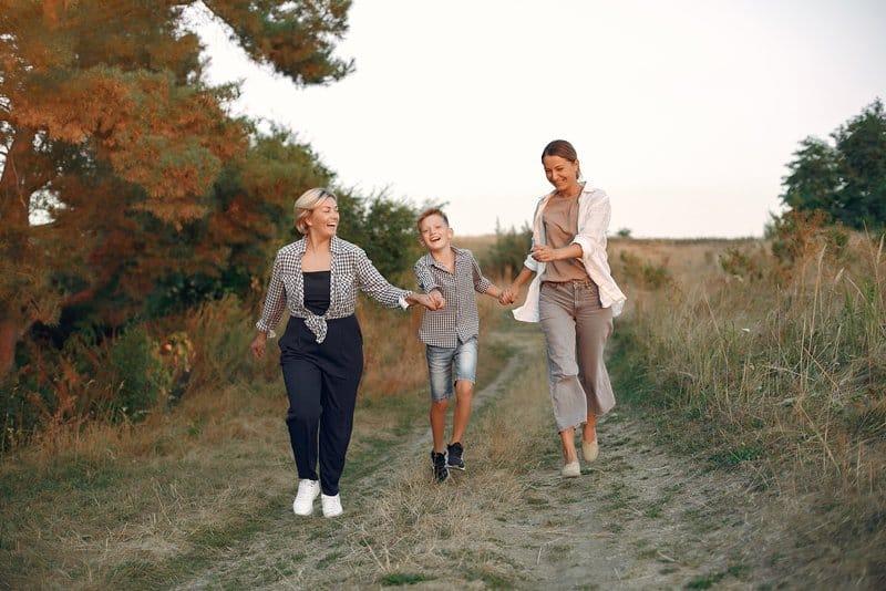 deux femmes et un enfant marchent joyeusement dans un champ