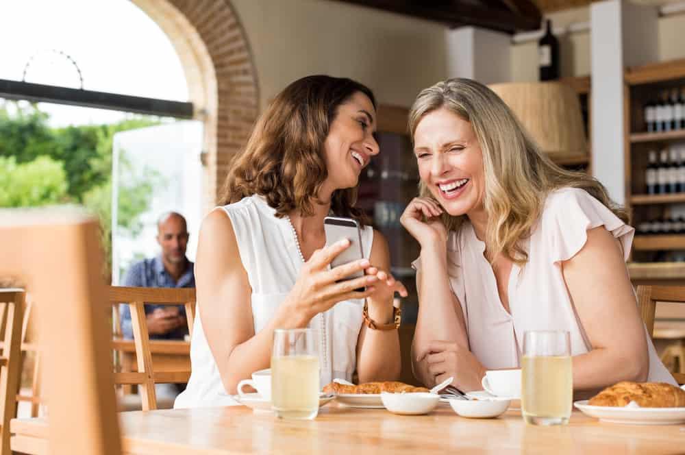 deux femmes prenant un café en riant
