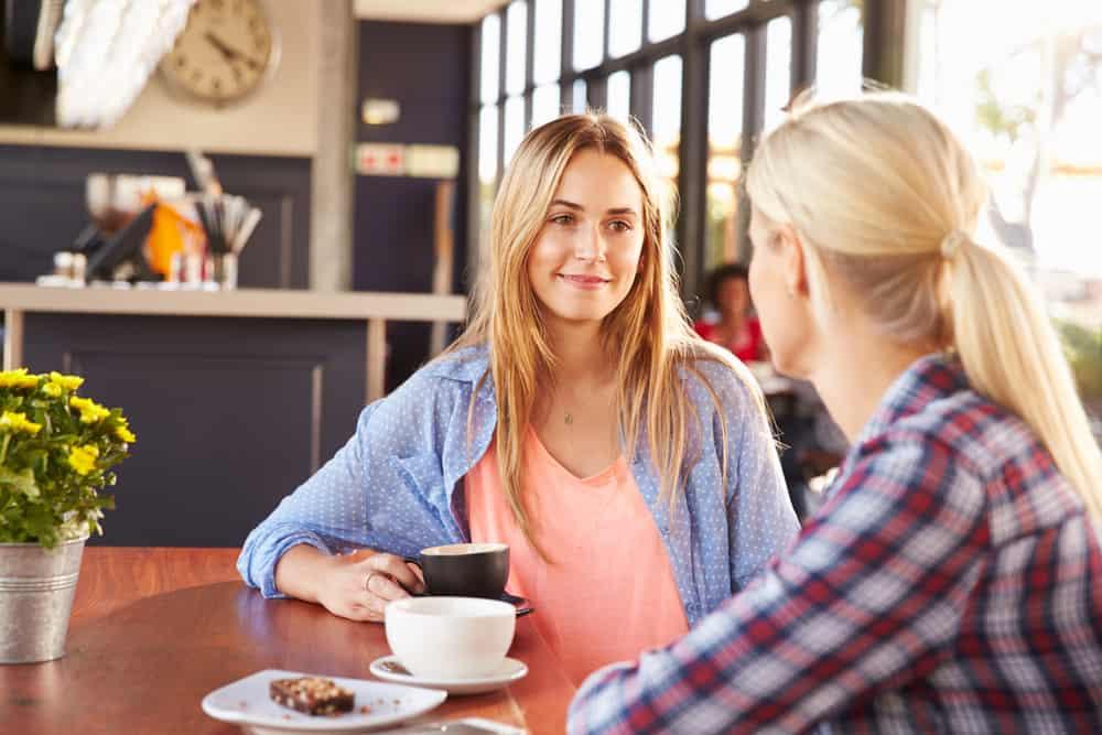 deux femmes s'assoient et boivent du café