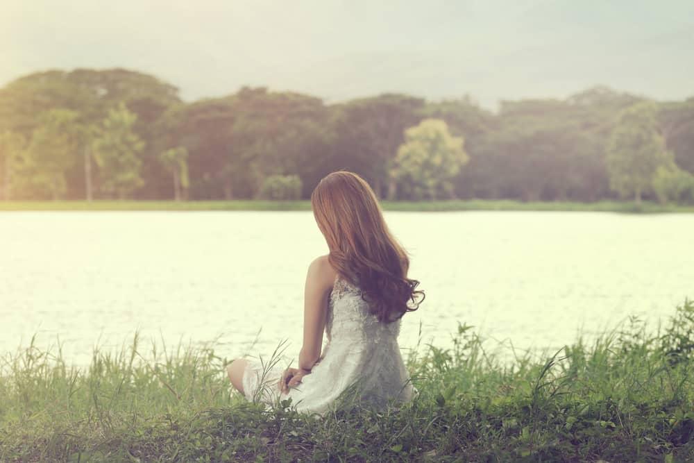femme assise sur l'herbe au bord de la rivière