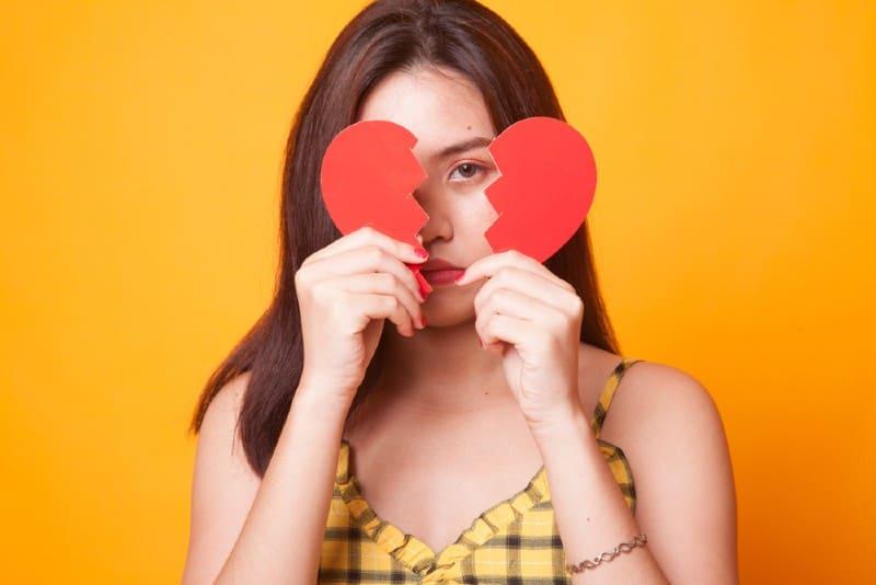 Belle jeune femme asiatique avec coeur brisé sur fond jaune